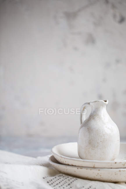 White ceramic plates and jug — Stock Photo