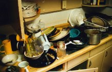 Low angle view of dirty kitchenware piled in sink at kitchen — Stock Photo