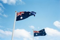 Flapping Australian flags in breeze over blue sky — Stock Photo
