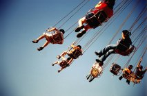 Rear view of children on flying swings — Stock Photo