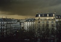 Evening cityscape with building facades under cloudy sky — Stock Photo
