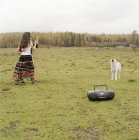 Couple dancing to music from tape device beside dog barking at countryside field — Stock Photo