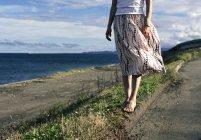 Low section of woman wearing dress standing on coastal roadside — Stock Photo