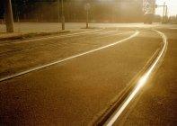 Carris do eléctrico na estrada de asfalto, refletindo a luz solar em cena de rua — Fotografia de Stock