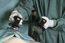 Ernte-Hände mit Defibrillator Maschine über Patienten — Stockfoto