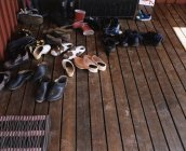 High angle view of pile of shoes on wooden boards floor — Stockfoto