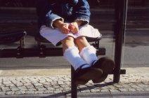 Crop girl seduta sulla panchina alla fermata dell'autobus — Foto stock