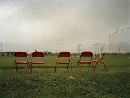 Row of red chairs beside football field — Stock Photo