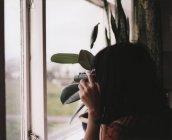 Vista laterale della donna che guarda fuori dalla finestra attraverso il binocolo — Foto stock