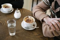 Close up view of cup of cappuccino and glass of water at cafe table with people — Stock Photo