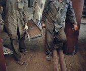 Crop workmen in boiler suits carrying iron beam — Stock Photo