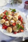 Close up view of choux pastry and chopped strawberries on plate at table — Stock Photo