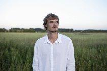 Jovem homem de camisa branca em pé no campo e olhando para longe — Fotografia de Stock