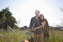 Casal com dois braços em pé no campo com bicicleta — Fotografia de Stock