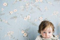 Retrato de um bebê na frente do papel de parede floral — Fotografia de Stock