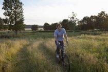Vélo jeune homme dans le champ — Photo de stock