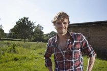 Young man standing in field with barn on background — Stock Photo