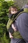 Отец, несущий свою маленькую дочь в детской коляске, сфокусированный на ребенке — стоковое фото