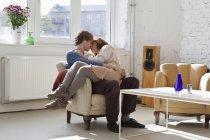 Молодая женщина, сидящая на коленях у своего парня и целующая — стоковое фото