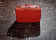 Vista di alto angolo della valigia rossa piano — Foto stock