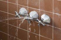 Gebrochener Duschgriff versprüht austretendes Wasser — Stockfoto