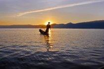 Silhouette de personne se tenant debout sur le bateau au lac au crépuscule — Photo de stock