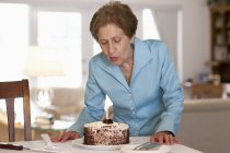 Senior woman blowing out a candle on a cake — Stock Photo