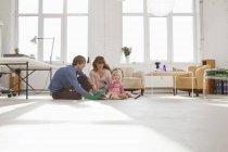 Una giovane famiglia hip che gioca insieme sul pavimento del soggiorno — Foto stock
