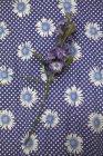 Flores púrpuras tallo en tela floral - foto de stock