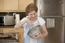 Portrait of senior woman mixing ingredients in bowl — Stock Photo
