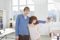 Молода грайлива пара, що стоїть пліч-на-пліч тримає руки — стокове фото