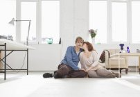 A young affectionate couple sitting side by side on the floor — Stock Photo