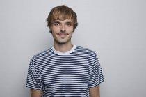 Молодой, бедный мужчина в полосатой футболке — стоковое фото