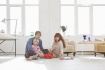A young family playing with toys on the living room floor — Stock Photo