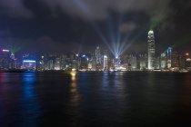 Paisaje urbano de iluminados Hong Kong visto del agua por la noche - foto de stock