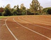 Vides pistes d'athlétisme au stade le jour ensoleillé — Photo de stock