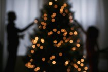 Silhouette di madre e figlia che decorano l'albero di Natale — Foto stock