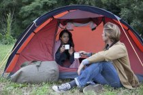 Casal jovem tendo bebida na barraca da abóbada — Fotografia de Stock