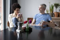 Cheerful couple enjoying breakfast together in dining room — Stock Photo