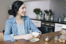 Felice giovane donna che prende il caffè guardando lontano in cucina — Foto stock