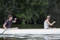 Young couple rowing canoe on lake — Stock Photo