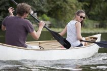 Young couple rowing canoe on lake — Stock Photo