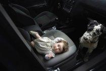 Lächelndes Baby auf Sitz liegend und portugiesischer Wasserhund im Auto — Stockfoto