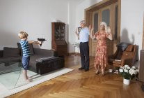 Boy aiming with toy gun towards grandparents at home — Stock Photo