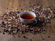 Tea cup amidst herb petals on wooden table — Stock Photo
