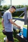 Hombre joven vertiendo café de la olla en el parque - foto de stock