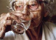 Mujer mayor bebiendo un vaso de agua - foto de stock