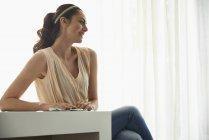 Sorrindo mulher pensativa olhando para longe enquanto sentado à mesa — Fotografia de Stock
