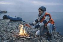 Teenage girl warming hands over bonfire on lake shore — Stock Photo