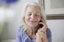 Deliziosa donna anziana che risponde al telefono cellulare a casa — Foto stock